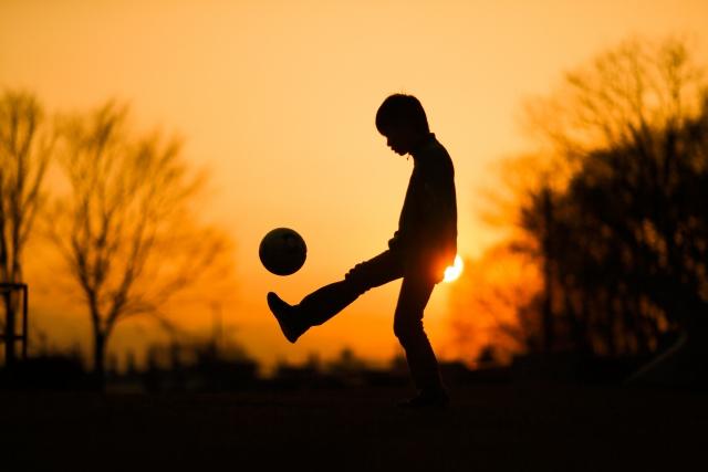 夕日 子ども サッカー 寂しげ